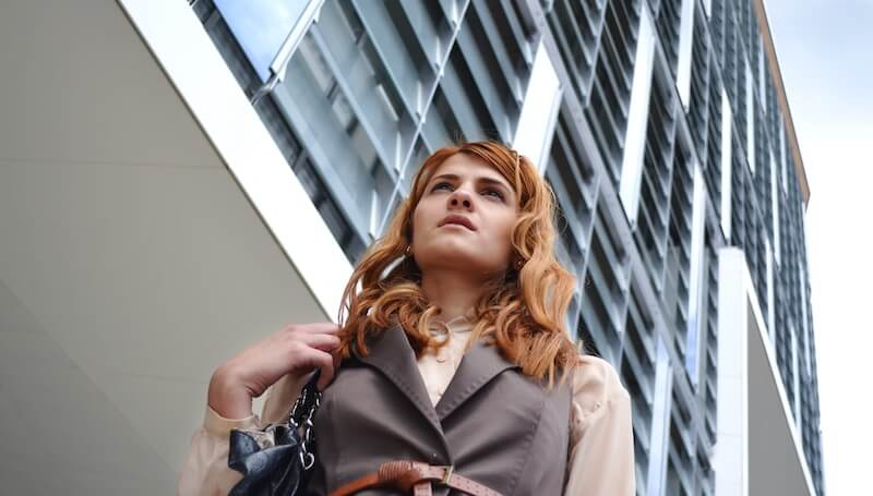 woman standing outside of tall building